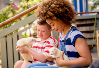 Two children hold ferrets