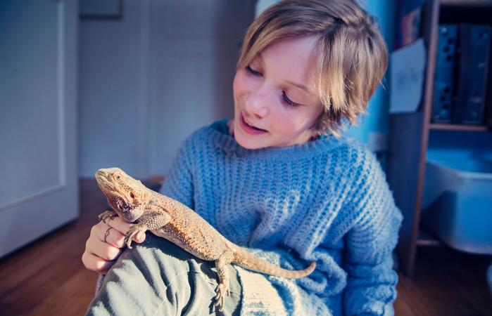 girl playing with her lizard pet
