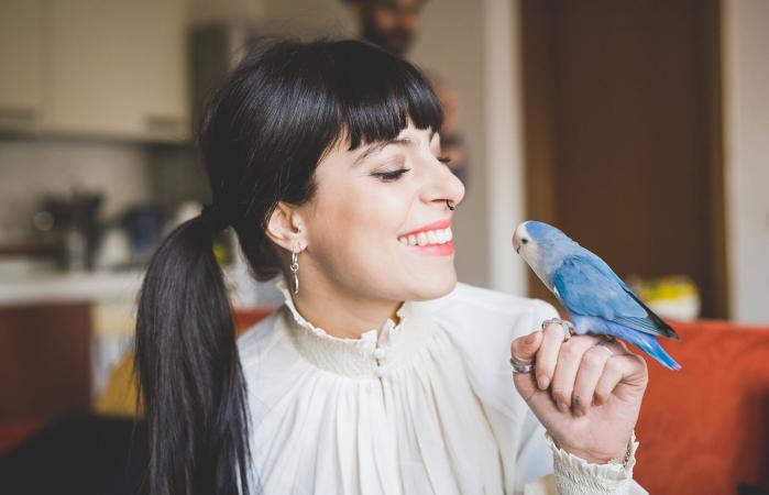 woman smiling at pet bird