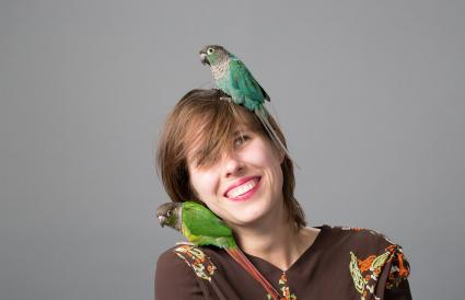 Woman with two parakeets