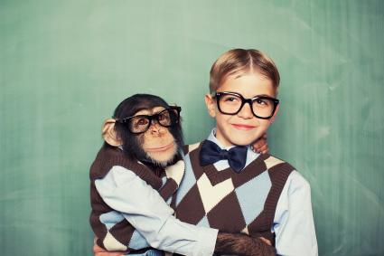 Young boy and a monkey dressed alike in classroom