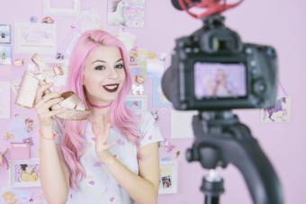Pink vlogger holding fashion shoe