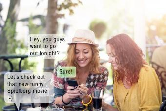 Two happy friends texting