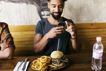 Man Taking Photos Of Burger With Smartphone