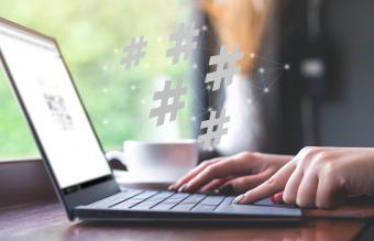 Woman using laptop with hashtag icon