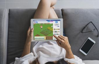Woman Playing Farm Town on Tablet