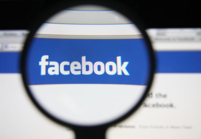 Facebook website through a magnifying glass