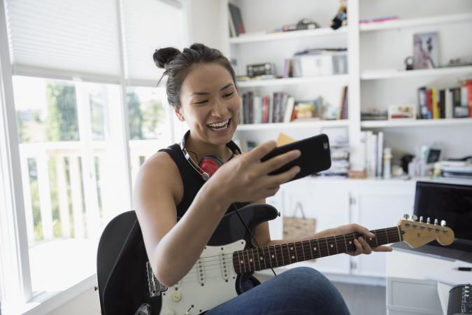girl on cell holding electric guitar