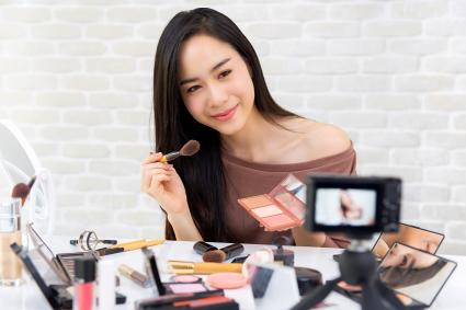 Woman professional beauty vlogger recording makeup tutorial video