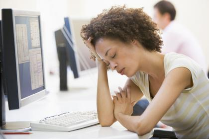 Stressed and tired woman at her office desk