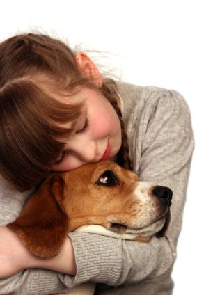 A child cuddling a dog