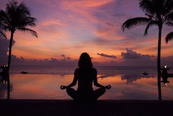 silhouette of woman meditating near pool