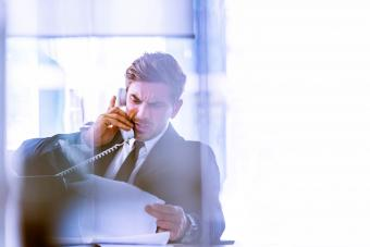 An anxious business executive talking to the phone while looking some paperwork