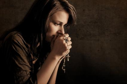 A woman praying holding a rosary