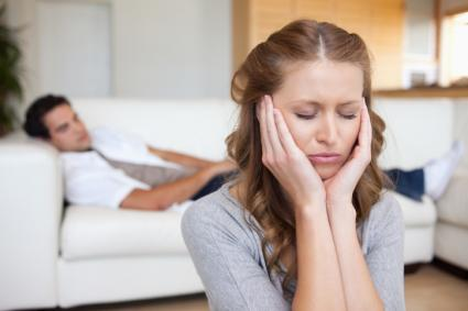 Woman with a headache man on sofa behind her