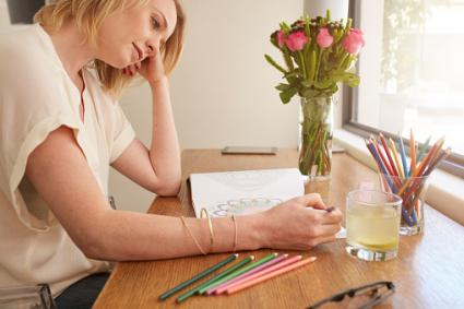 Woman relaxing at home with coloring book