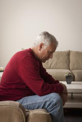 depressed senior man alone on couch