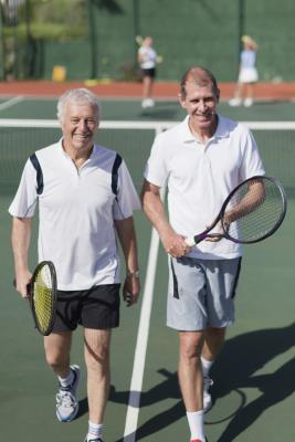 Senior men playing doubles tennis