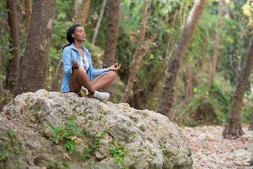 woman meditating in forest
