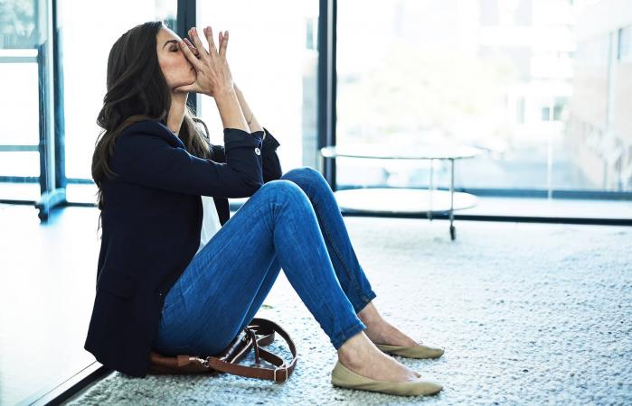Stressed businesswoman sitting on the floor