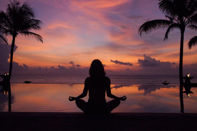 silhouette of woman meditating near pool