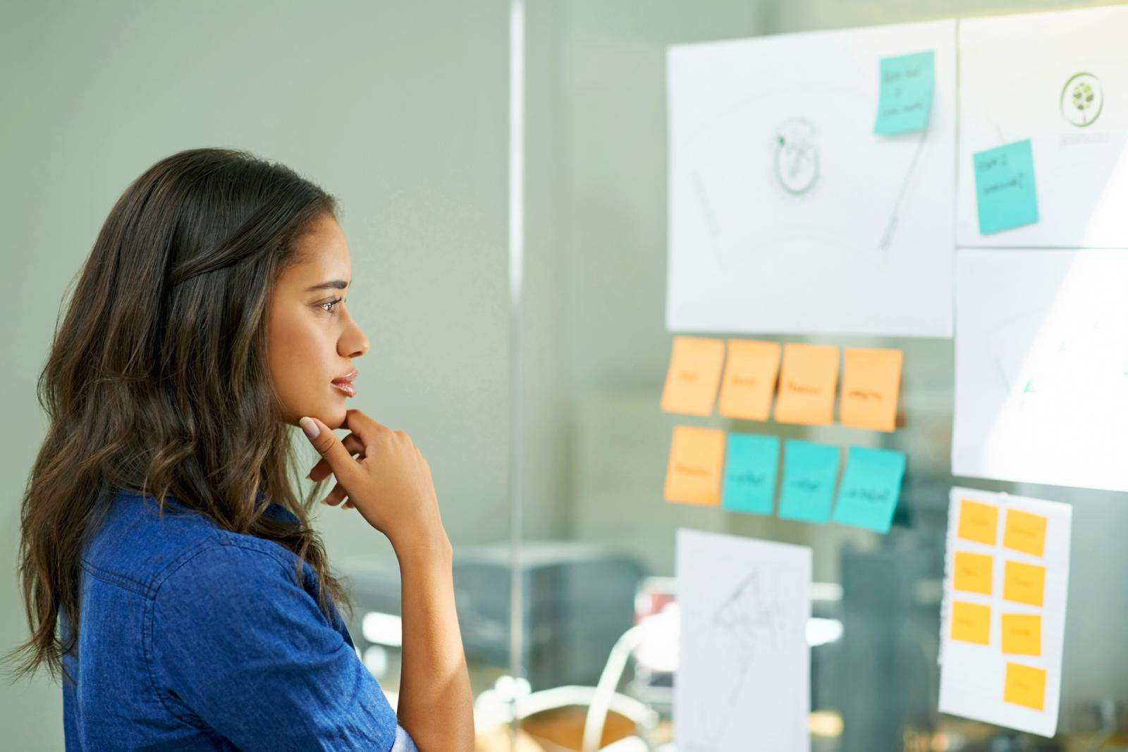 Young woman brainstorming with sticky notes at work