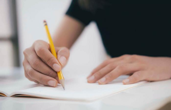 hands with pen writing on notebook