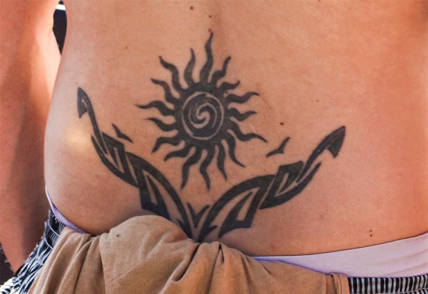 https://cf.ltkcdn.net/tattoos/images/slide/178457-850x583-sun-lower-back-tattoo.jpg