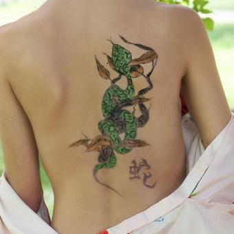 Green snake tattoo on back