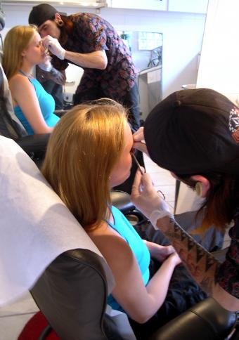 girl getting nose pierced