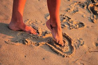 Foot drawing heart in sand