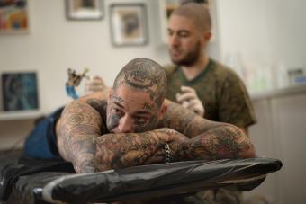 Tattoo artist working on heavily tattooed man