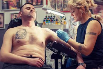 Female tattoo artist giving man a tattoo