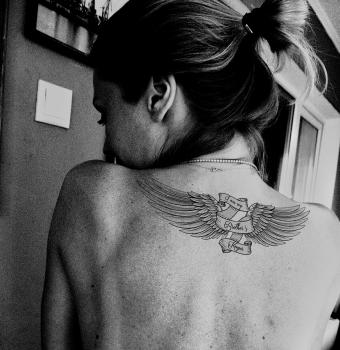 Winged Brother's Keeper tattoo on woman's back
