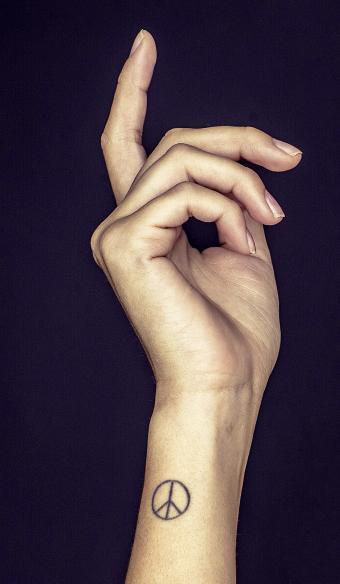 Small peace tattoo on woman's wrist
