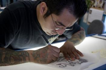 Tattoo artist designing a tatoo