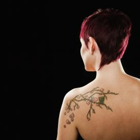 Woman With Blossoms Tattoo on Back
