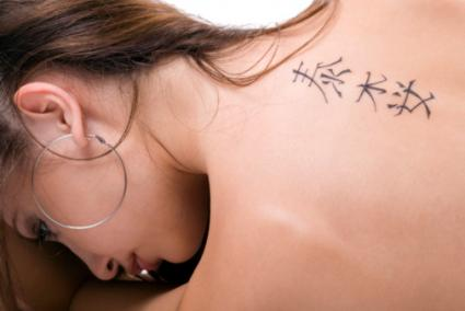 Young woman with Japanese tattoo down spine