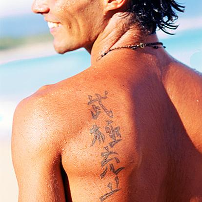 Chinese symbols tattooed on man's shoulder