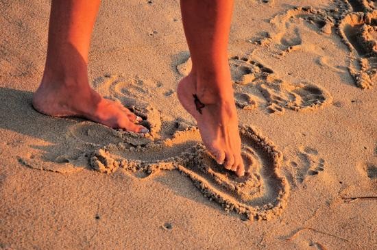 5cd22908f Foot drawing heart in sand