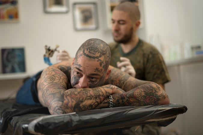 Tattoo artist working on heavily tattooed man