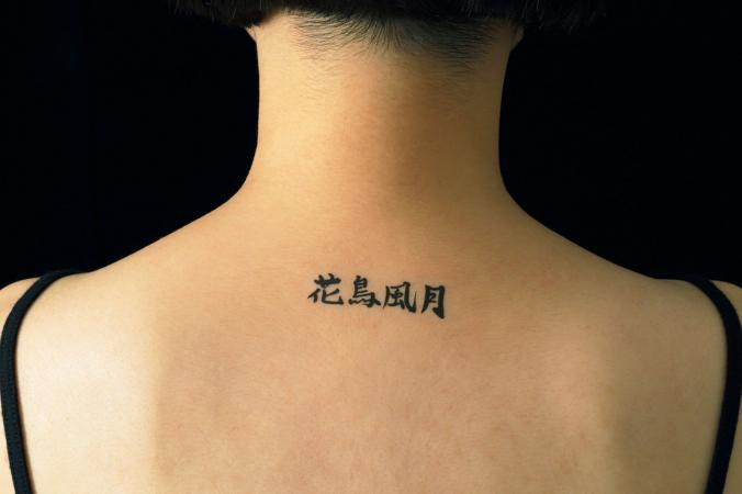 Woman with Chinese tattoo on shoulder