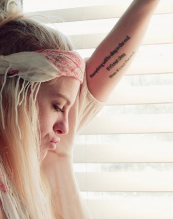 Hippy girl with forearm quotation tattoo