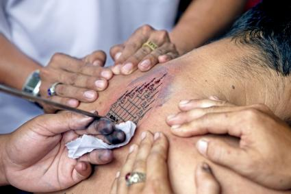 Thai Buddhist monks tattooing at temple
