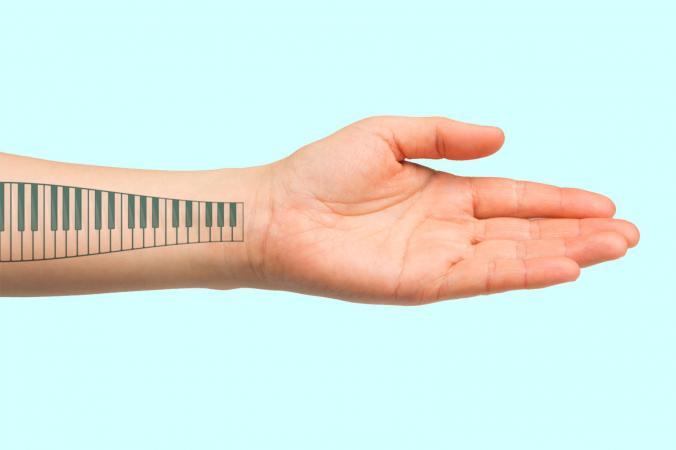 piano keyboard tattoo on forearm