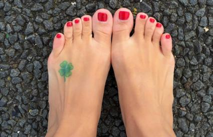 Woman's feet with four leaf clover tattoo