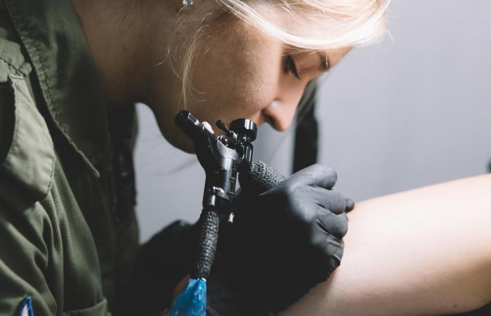Tattoo artist covering scar on arm
