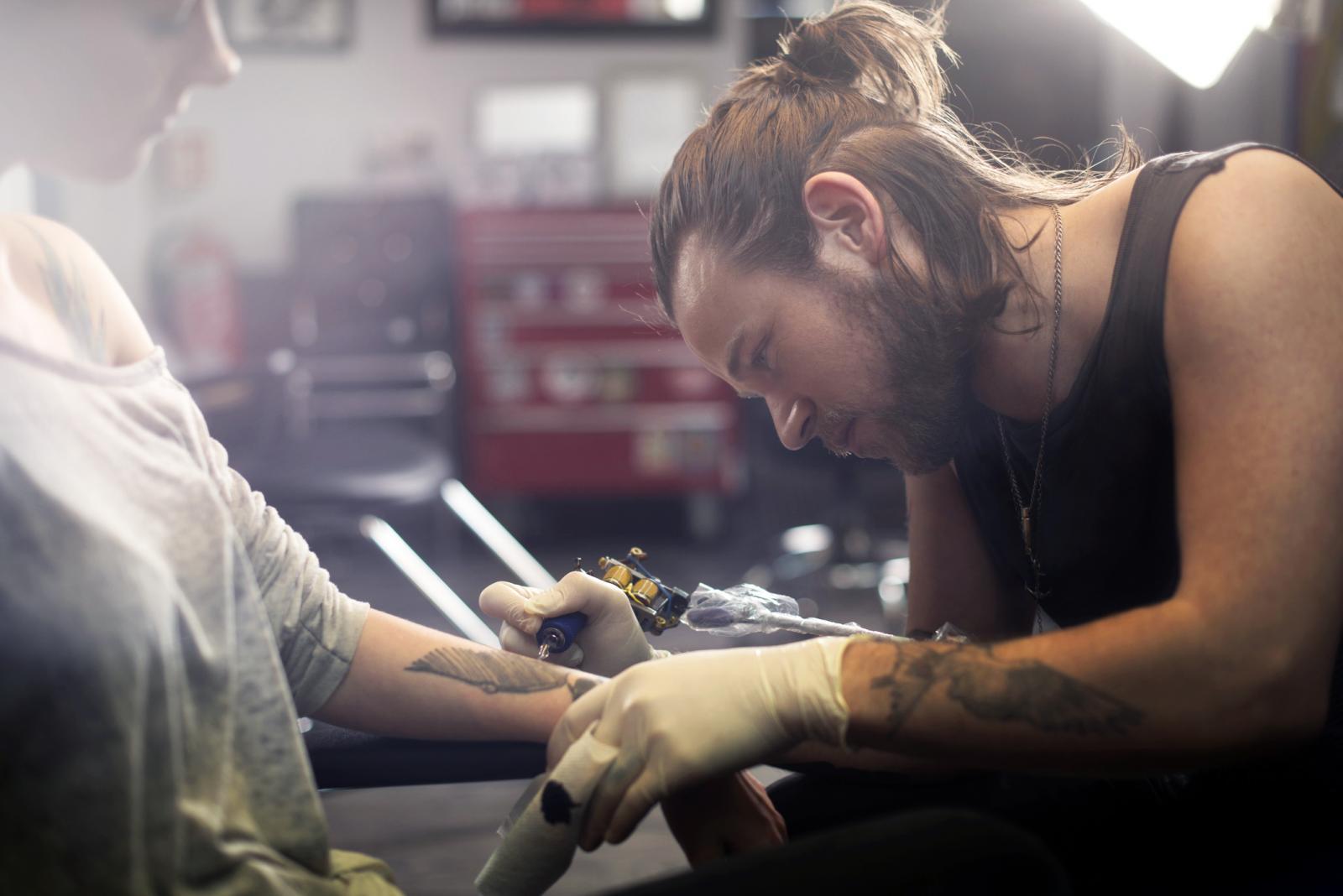 Tattoo expert is working in studio