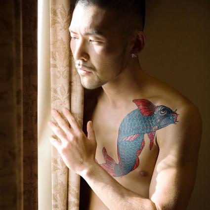 hombre con tatuaje azul koi