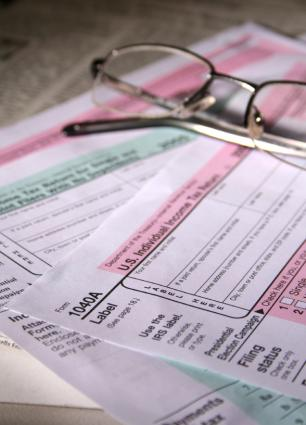 multiple tax forms with glasses